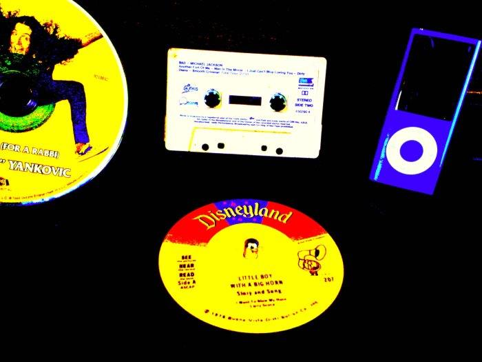 Photograph of Disney Vinyl Record, Weird Al Yankovitch CD, Michael Jackson CD and purple ipod representing the ages of music
