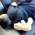 Photograph of my husband Earth sleeping on the couch with my Son Storm's favourite white teddy bear